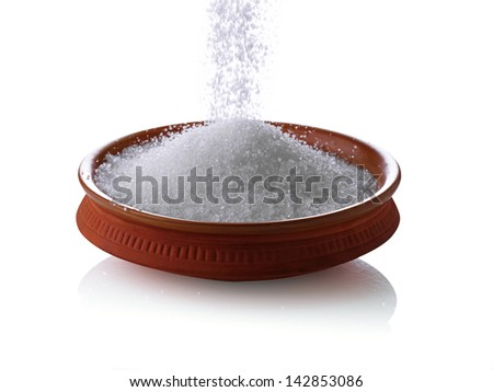 sugar being poured into a bowl