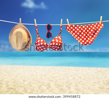 Summer Beach clothes and accessories stylish set. Fashion swimsuit bikini red polka dots, sunglasses hat. Essentials creative look on tropical sea sky background.Hawaii, ocean vacation.Vintage - stock photo