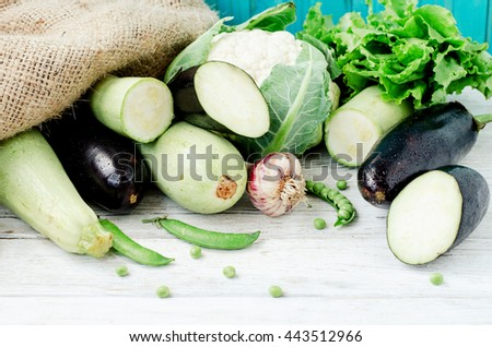 Summer fresh ripe vegetables,blue eggplant , green zucchini , peas, cauliflower, lettuce and garlic on a wooden background