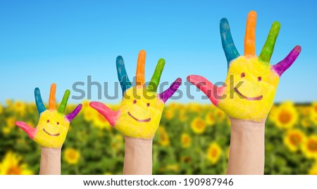 Summer holidays and family concept. Three colorful painted hands with smiling face of family, mother, father and baby on background of sunflowers field in sunny summer's day. - stock photo