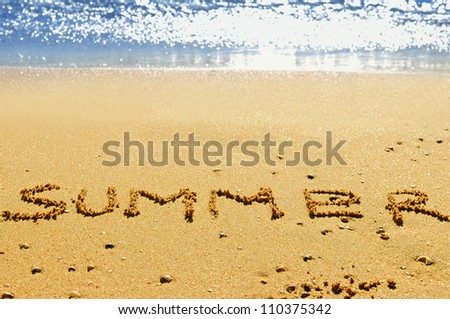 """Summer"" ; written in the sand on the beach with blue waves in the background - stock photo"
