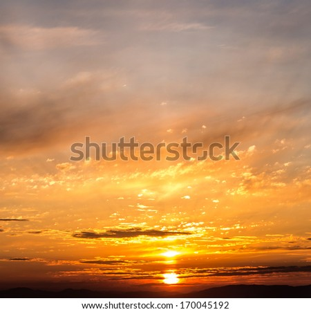 Sunset with clouds and light rays.  - stock photo