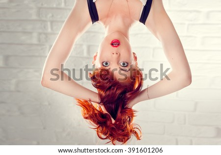 Surprised green-eyed girl upside down - stock photo