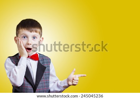 Surprised Pointing little boy isolated over yellow background. - stock photo