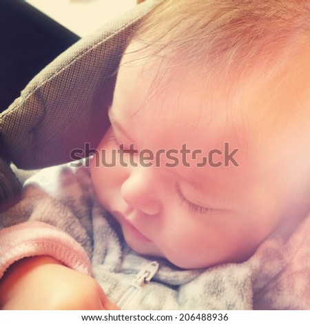 Sweet baby sleeping in baby carrier - With Instagram effect - stock photo