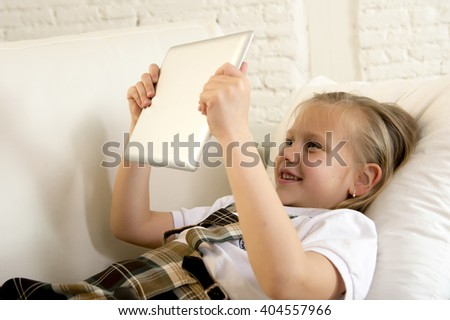 sweet cute and beautiful 6 or 7 years female child with blond hair in school uniform lying on home sofa couch using internet app on digital tablet pad playing online game smiling happy - stock photo