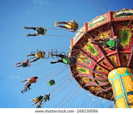 Swing ride at fair spinning around with people having fun  - stock photo