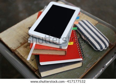 tablet on book, using mobile ipad, Internet of things lifestyle with wireless communication and internet with smart phone and tablet. copy space