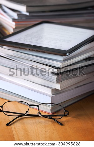 tablet put on book pile - stock photo