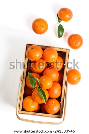 tangerines with fresh leaves in wooden box isolated on white, isolated on a white, top view  - stock photo