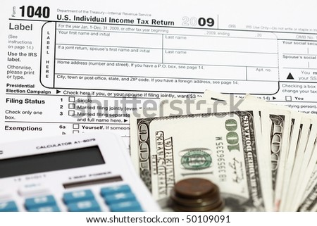 1040 tax form with calculator and dollars.