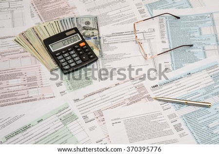 1040 tax form with calculator, pen and dollar bills