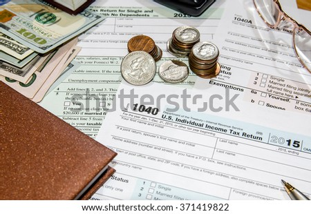 1040 tax form with dollar, glasses, mouse, calculator, notepad