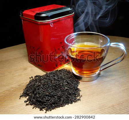 tea tan and warm tea cup over black background - stock photo