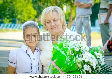 Teacher and pupil. girl gives flowers a school teacher in teacher's day