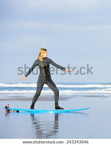 teaching young woman to surf - stock photo