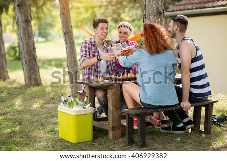 Team of young people having fun and playing chess in summer camp in wood