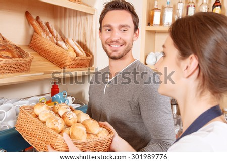 Team work. Male and female bakery workers setting out goods on stalls - stock photo