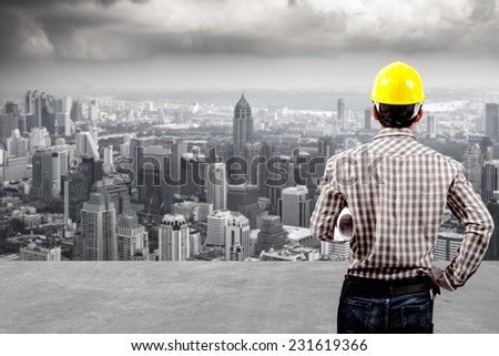 technician builder in protective safety equipment goggles hard hat and blueprints working at high building construction site against urban scene balcony over looking city dusky before rain falling  - stock photo