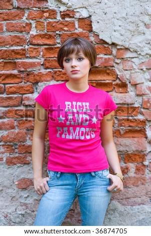 teen girl next to brick wall - stock photo