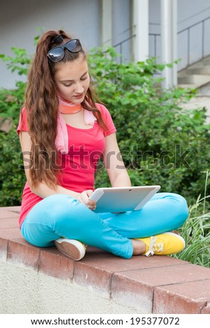 teen girl using a tablet pc sitting outdoors