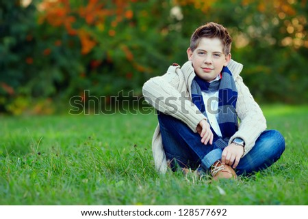 teenage boy on green grass, outdoors - stock photo