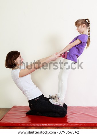 Teenage girl and a physiotherapist are doing an exercise - stock photo