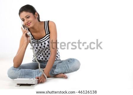 Teenage girl sitting on the floor talking over telephone - stock photo