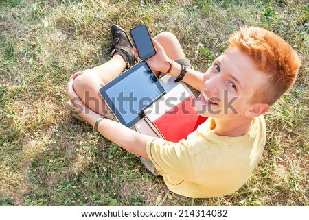 Teenager is using tablet computer and smart phone.  - stock photo