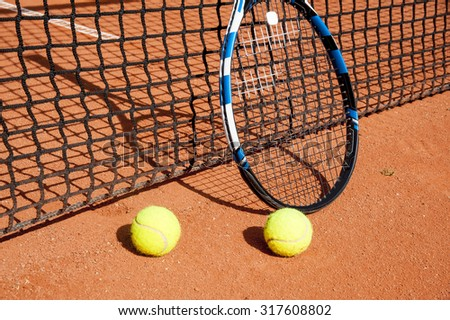 Tennis balls  and  racket  at the net on a red  unpaved field