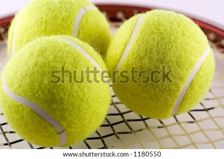3 tennis balls on a racquet - stock photo