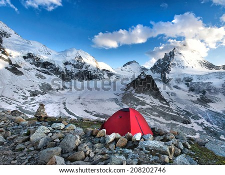 tent in mountain wit high peaks in mountains - stock photo