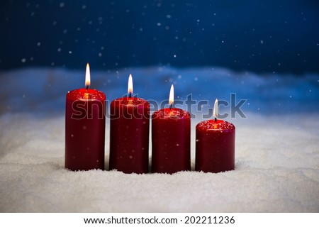 4th Advent candle in snow and snowfall - stock photo