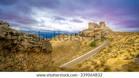 12th-century castle, located at Consuegra, Castilla - La Mancha, Spain. Close to the castle, there are a few traditional windmills, like those described by Cervantes in the Don Quixote book.