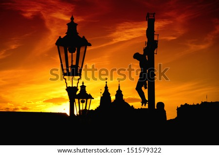 17th Century Crucifixion statue on Charles Bridge in Prague, Czech Republic. Image is taken against the light in the sunset. - stock photo