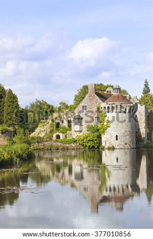 14th century moated English medieval castle Scotney in Kent countryside , surrounded by romantic gardens, woodlands, with ruins reflected in the lake full of floating water white lilies . - stock photo