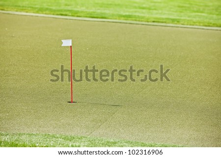 7th hole on the golf course with artificial grass and white flag on the red stick - stock photo