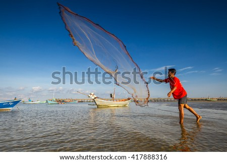 10th May 2013 at Chao Laow Beach in Chanthaburi province in east of Thailand : unidentified man throw fishing net to sea water to catch small fish