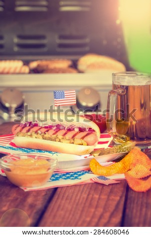 4th of July Picnic Table With Hot Dog and Grill in the background - stock photo