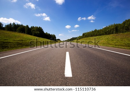 the asphalted road to summertime of year - stock photo