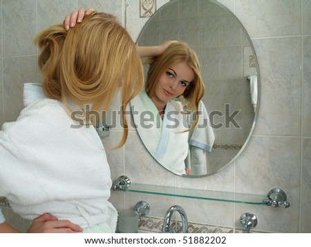 The beautiful girl with bond hair looks in a mirror in a bathroom