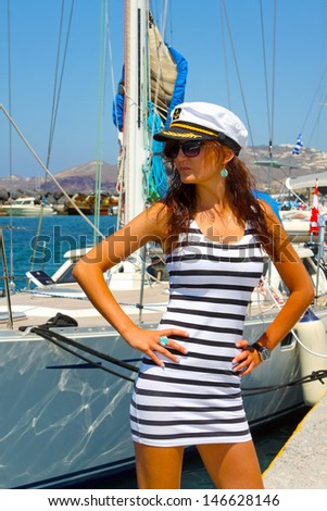 The beautiful trendy girl in a striped dress and a peak-cap of the captain in island Santorini port. Greece - stock photo