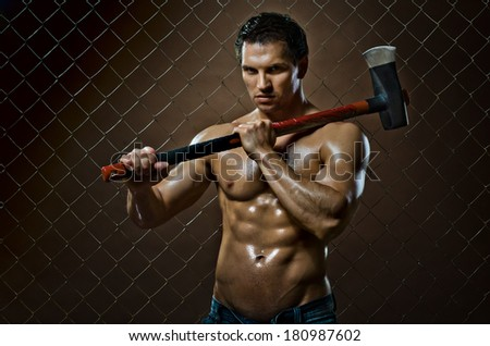 the beauty muscular worker chopper man  with big  heavy ax  in hands, tired  appearance , on netting fence background - stock photo