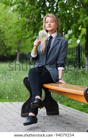 The blond girl sits in park - stock photo