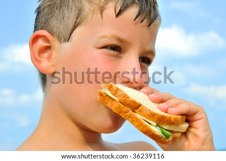 The boy bites sandwich with cheese and cucumber