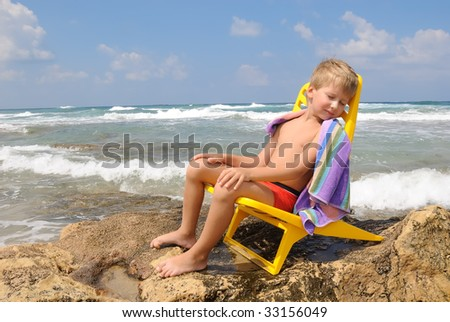 The boy rests after swimming in a chair on the stone on the beach