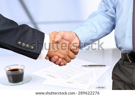 The Close-up image of a firm handshake between two colleagues under contract - stock photo