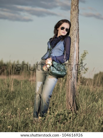 The girl in sunglasses costs at a tree