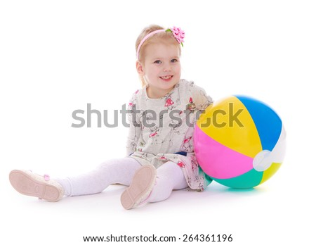 The girl with the ball sitting on white background - isolated on white background - stock photo
