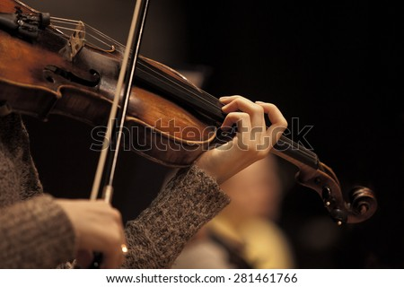 The hand of the girl playing the violin in dark colors - stock photo
